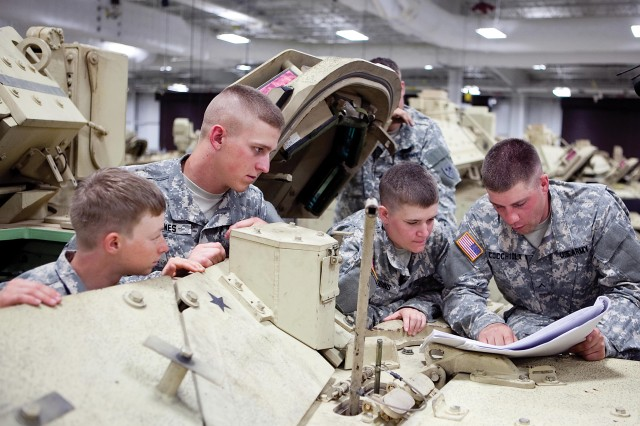 Pvt. Christy Bailey (left) and  Pvt. Taylor Robbins (second from right) were two of five of the first female Soldiers to graduate the 91M Bradley Fighting Vehicle maintainers course, May 31, 2013, on Harmony Church at Fort Benning, Ga.