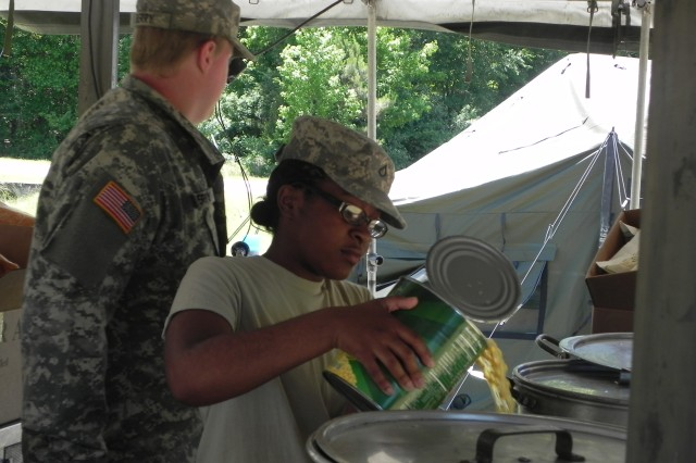 "U.S. Army Pfc. Kennice Parker with the 611th Quartermaster Company, prepares one of her first meals in a field environment during the Quartermaster Liquid Logistics Exercise held at Fort A. P. Hill, Va., June 4, 2013. Parker was excited to be participating in QLLEX, saying, ""This is my first time cooking since AIT."""