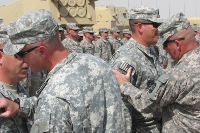 Lt. Col. J.P. Maddaloni 1st Battalion, 14th Field Artillery commander (left), places the 214th Fires Brigade combat patch on Capt. Brandon McKean. Command Sgt. Maj. Daniel Nolen also awards 1st Sgt. Kevin Carter with his combat patch. The battalion hosted the ceremony May 30, 2013, to recognize those Soldiers who earned their patches following 30 days of service in the United Arab Emirates.