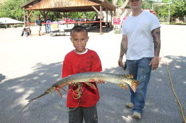 "Tristen Matz, age 7, landed the most unusual fish in the kids' fishing derby  a needlenosed gar that took ""a little while"" to get on the bank. Gar sport a snout full of razor sharp teeth, and though they don't look it, are quite tasty for the person who knows how to clean and cook them."