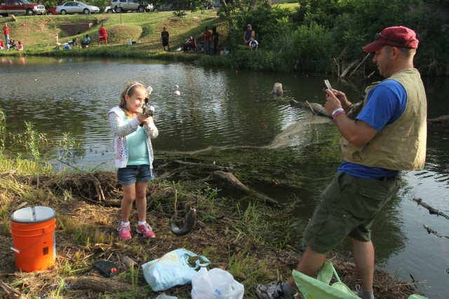 Greg Marcum takes a photo of his daughter, Karlie, and a hefty catfish she caught on a piece of hot dog during the annual kids' fishing derby June 1 on Medicine Creek at Fort Sill.