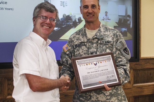 Anniston Army Depot Commander Col. Brent Bolander presents Matt Hunter, chief of the depot's Managerial Accounting Division, with the AMC Personnel of the Year award. Hunter is one of 12 recipients from throughout AMC to be honored with the Louis Dellamonica Award for 2012.