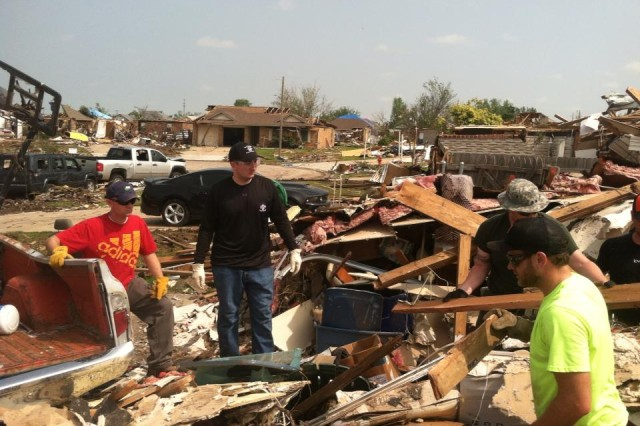 First Lt. Mark Keel (left) and Capt. Erik Anthes (in black) salvage a home with a team of other veterans Memorial Day weekend in Moore, Okla. Keel is executive officer for Co. E, 1st Bn., 16th Inf. Regt., 1st ABCT, 1st Inf. Div., and Anthes is the company's commander. They spent their holiday weekend in the Oklahoma City suburb with a group of active and former servicemembers assisting cleanup efforts.
