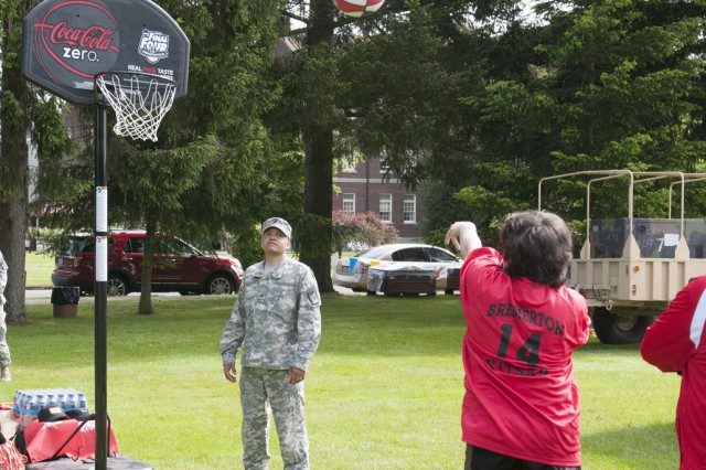 "JOINT BASE LEWIS-McCHORD, Wash. "" Sgt. Jonathan Bonet, 47th Combat Surgical Hospital, helps retrieve basketballs and cheers on competitors visiting Joint Base Lewis-McChord, Wash., for the annual Washington State Special Olympics, June 1. This is the second year Bonet volunteered for the event with his unit and continues to be motivated by the level of competition and motivation he sees from the athletes."