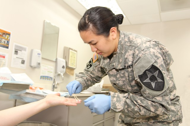 Capt. Mylinh Bruhn, the brigade nurse assigned to Company C, 302nd Brigade Support Battalion, 1st Armored Brigade Combat Team, 2nd Infantry Division, collects forensic materials during a recent Sexual Assault Medical Forensics Examiners course, held at Camp Humphreys, South Korea, in May.