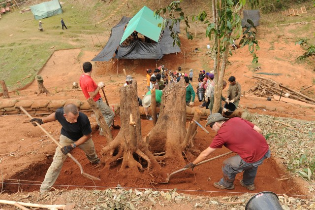 Sgt. Benjamin Koehn and Air Force Staff Sgt. Austin Weinman dig around the base of a tree, Jan. 28, 2013, at a recovery site in Xekong Province, Laos. Fourteen personnel from the Joint POW/MIA Accounting Command deployed to Laos in search of air crew members missing from the Vietnam War.