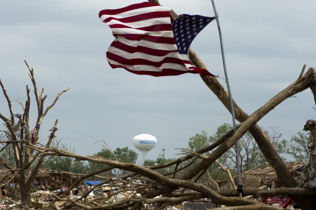A flag blows in the wind on May 27, 2013, over the rubble left in the wake of the May 20 EF-5 tornado that ripped through parts of Moore, Okla. The storm killed 24, injured hundreds and damaged thousands of homes.