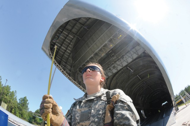 Pvt. Devinne Crawford holds measuring tape for the purpose of measuring the height of a pallet her team built during the Transportation Managment Coordinator Course field training exercise May 30. Crawford and her team members were required to build the pallet to specifications to test their problem-solving skills