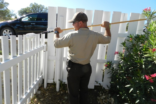 Darren Hall, Make Ready Team laborer, paints the fence that encloses the back yard of the Sanford House along the historic row of homes. Repainting the white picket fences is one of many projects the MRT takes on for the maintenance and landscaping of Mountain Vista Communities.
