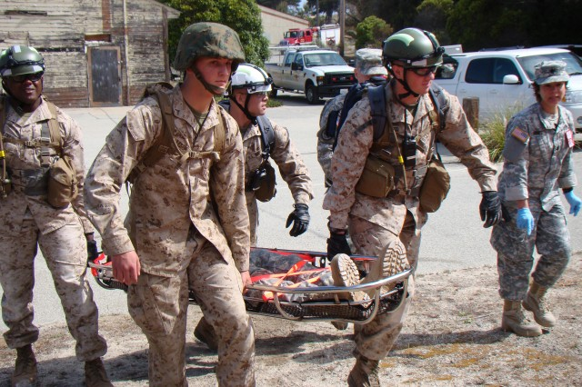 "PRESIDIO OF MONTEREY, Calif. - Members of the Presidio of Monterey's Marine Corps Detachment Search and Rescue team carry a mock casualty to the triage area before turning over the ""patient"" to California Medical Detachment staff (shown in background)."