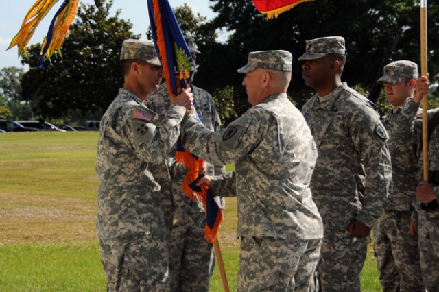 Lt. Col. James E. Ward (right, center), relinquishes command of the 1st Battalion, 145th Aviation Regiment by passing the unit's colors to Col. Brian D. Bennett (right), commander of 1st Aviation Brigade, May 29 at Howze Parade Field during a change of command ceremony.