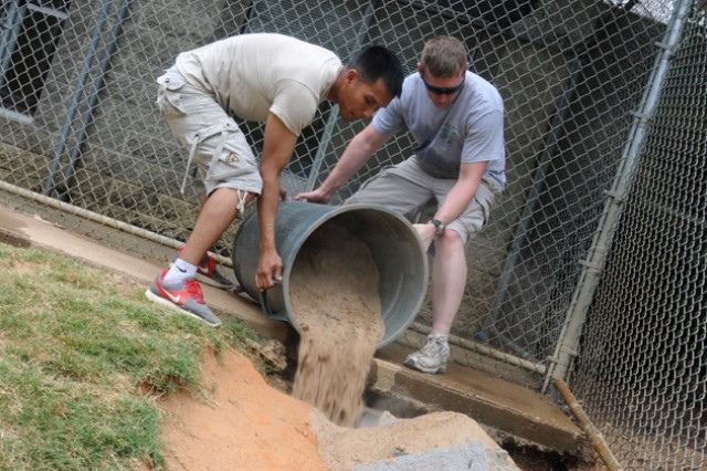 WO1 Jonathan Reabe and WO1 Toe Wai, B Company, 1st Battalion, 145th Aviation Regiment, fill in holes with concrete and sand at the Wiregrass Humane Society June 1. Soldiers from the Viking and Charger Flights teamed up to help improve the quality and safety of the WHS grounds and buildings for both people and animals.