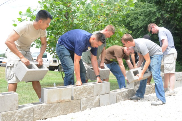 Soldiers of B Co., 1st Bn., 145th Avn. Regt., line the driveway at the Wiregrass Humane Society with concrete blocks June 1. Soldiers from the Viking and Charger Flights teamed up to help improve the quality and safety of the WHS grounds and buildings for both people and animals.