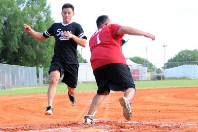Frank Yu, player for the Sauce All-Stars, attempts to beat the ball to home plate as Efrain Ramos, catcher for the Outcasts, catches the ball during an intramural softball game at the Fort Rucker softball fields June 3. The Outcasts went on to beat the Sauce All-Stars 14-12.