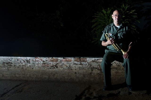 SONSONATE, El Salvador- Salvadoran Army musician, Luis Alfredo Henriquez-Lopez, Military District Six, waits for his 9 p.m. cue to sound off his last bugle call of the day. Henriquez is currently supporting Beyond the Horizon-El Salvador 2013,  a U.S. Southern Command-sponsored, Army South-led, joint foreign military interaction and humanitarian exercise that supports the host nation through engineering projects and medical, dental and  veterinarian exercises that assist the people in certain areas of El Salvador.