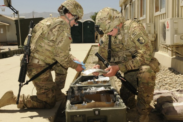 Spc. Nicole C. Chojnacky (left) a native of Jerome, Idaho and Spc. Brodie C. VanBrunt (right) a native from Riverton, Wyo., both medics with Task Force Lifeliner, gather medical supplies during their training exercise June 7, 2013 at Bagram Airfield in Afghanistan. The training known as MASCAL (mass-casualty) prepares medics for situations where the number of casualties exceeds the aid station capabilities to provide medical care.