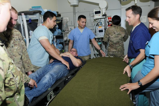 Chef Robert Irvine, traveling with the Operation H.O.T. team, plays the role of a patient being received for treatment, June 6, as part of the team's tour of Role 3 Multinational Hospital in Kandahar Airfield, Afghanistan. (U.S. Army photo by Sgt. Uriah Walker, RC(S) Public Affairs)