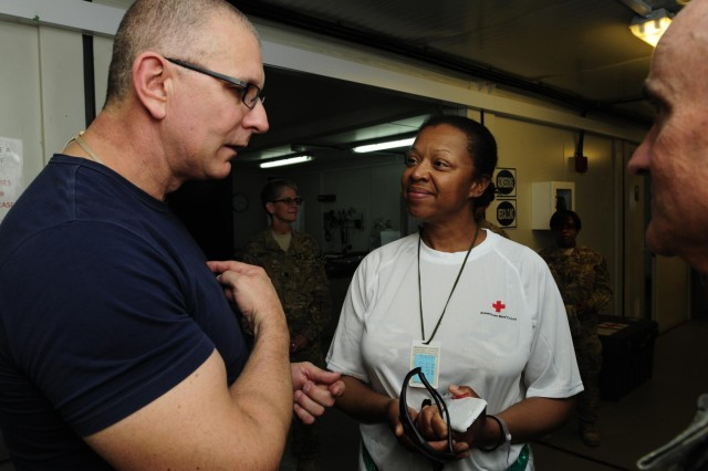 Chef Robert Irvine speaks with Sgt. 1st Class Gina Pierce, a native of Thorofare, N.J., assigned to Headquarters and Headquarters Company, 501st Sustainment Brigade, Second Infantry Division, during a visit to the Warrior Recovery Center, June 6, in Kandahar Airfield, Afghanistan. During the conversation, Pierce offered a cooking date to Irvine who immediately accepted and committed to fulfill after her recovery and return to the U.S. (U.S. Army photo by Sgt. Uriah Walker, RC(S) Public Affairs)