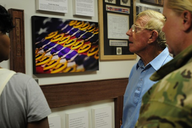 """College football coaching legend and ESPN analyst Lou Holtz pauses to recognize the """"Purple Heart"""" wall, June 6, during a tour of the Role 3 Multinational Hospital in Kandahar Airfield, Afghanistan. Holtz is visiting as part of Operation Honor Our Troops, founded in 2011 by Chef Charles Carroll, as a way to show support for the service members fighting abroad in the war on terror. (U.S. Army photo by Sgt. Uriah Walker, RC(S) Public Affairs)"""