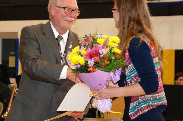 Vicenza High School music director Gary Marvel receives a bouquet from student musicians at the conclusion of the VHS Spring Concert May 29 in Vicenza, Italy.