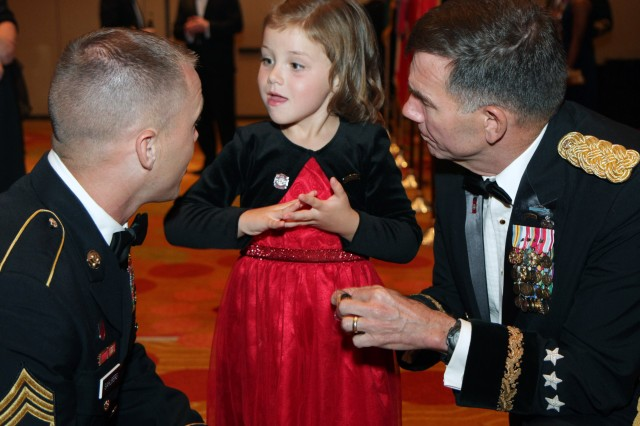 "SAN ANTONIO, Texas "" Amaya Sahlberg beams at her father, Staff Sgt. Adam Sahlberg, after Lt. Gen William Caldwell IV offers her one of his command coins June 1 at the 238th Army Birthday Ball at the Grand Hyatt in San Antonio. Caldwell is the commanding general of U.S. Army North (Fifth Army) and senior commander Fort Sam Houston and Camp Bullis; Sahlberg serves as a writer and instructor for the Center for Pre-Deployment Medicine, 32nd Medical Brigade."