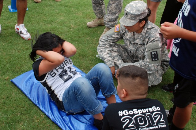 Spc. Laura Calderon encourages a student to pump out as many sit-ups as she can during Columbia Heights Elementary School's field day May 1. Calderon and other Soldiers from the 717th Military Intelligence Battalion volunteered for the community outreach event. (U.S. Army photo by Gregory Ripps, 470th Military Intelligence Brigade)