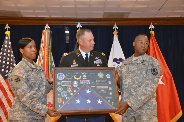 Lt. Col. Jacqueline L. Patten, chief of Current Operations, G-33, U.S. Army Space and Missile Defense Command/Army Forces Strategic Command, and Col. Lorenzo Mack Sr., deputy chief of staff, G-3, present Col. Eric P. Henderson chief, G-33 Division Operations, with a shadow box for his 27 years of military service during a retirement June 7 at the Peterson Club, Peterson Air Force Base, Colo.