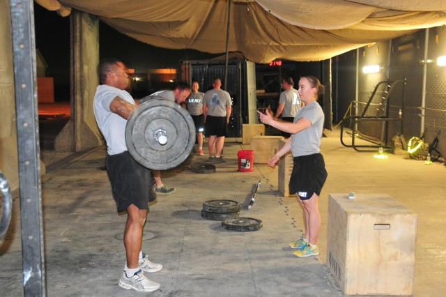 Capt. Ashley Nicolas, the assistant intelligence officer with Combined Task Force 4-2 (4th Stryker Brigade Combat Team, 2nd Infantry Division), coaches a fellow soldier during a CrossFit workout June 4 on Kandahar Airfield, Afghanistan. (U.S. Army photo by Sgt. Kimberly Hackbarth, CTF 4-2 PAO)