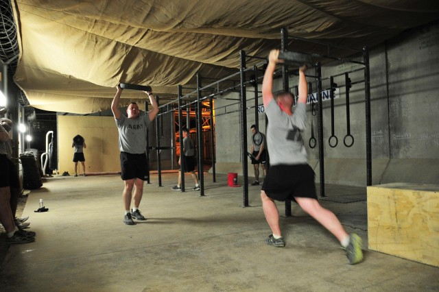 Soldiers with Combined Task Force 4-2 (4th Stryker Brigade Combat Team, 2nd Infantry Division) perform lunges while carrying weighted plates during a CrossFit workout June 4 on Kandahar Airfield, Afghanistan. (U.S. Army photo by Sgt. Kimberly Hackbarth, CTF 4-2 PAO)