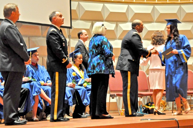 1st Lt. Rafael Chico-Lugo congratulates graduating senior Lauren Barry during the 2013 Commencement Ceremony for Wiesbaden High School in the Wiesbaden Kurhaus June 9 as DoDDS-E and fellow military officials look on.