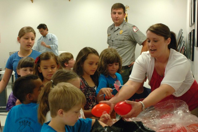 Mary Tipton, a biologist with the U.S. Army Corps of Engineers Nashville District Planning Branch, hands out water safety goodies to kids at the Williamson County Junior Gardener Camp at the Agricultural Exposition Park, June 7, 2013. Park Ranger Dean Austin had given the kids a water safety presentation and encouraged them to always wear a life jacket when playing in or around water.