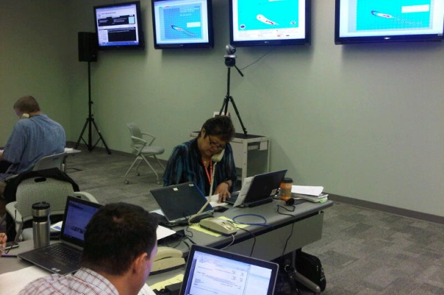 Lolly Silva, USACE-Pacific Ocean Division's Readiness and Contingency Operations officer calls the state Emergency Operations Center to inject an event from the exercise Master Scenario Events List at the Sim Cell for Exercise Makani Pahili 2013.  Pacific Ocean Division's Readiness and Contingency Operations Division supported the annual hurricane preparation exercise, which was coordinated by the state Civil Defense and the Hawaii National Guard.