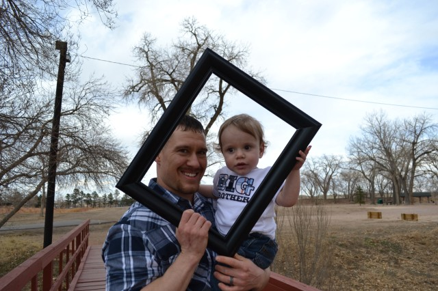 FORT CARSON, Colo. --Morgan Waterman and his son, Noah Waterman, play with a picture frame as they spend the day at Iron Horse Park, March 29, 2013. Morgan Waterman is a stay at home dad, who daily helps his son with a number of medical issues due to a premature birth and other conditions related to his mother, Capt. Rebecca Waterman, personnel officer, 759th Military Police Battalion, having a low blood platelet count, a condition that affects 3% of the population. (Photo courtesy of Capt. Rebecca Waterman, 759th Military Police Battalion)
