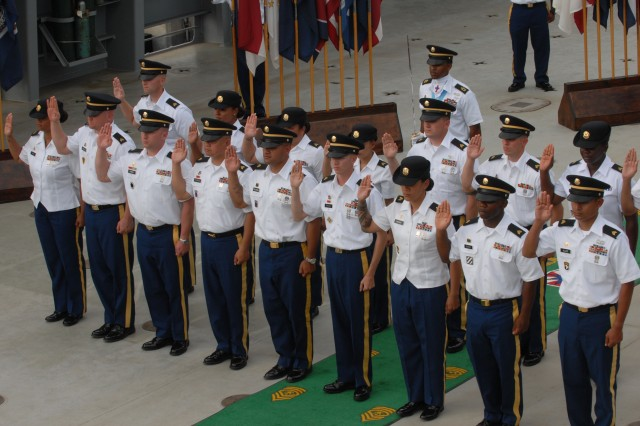 The 17 newly inducted noncommissioned officers from the 8th Special Troops Battalion, 8th Theater Sustainment Command, raise their right hand and recite the NCO Charge aboard the 9th Mission Support Command 's Logistic Support Vessel during a Noncommissioned Officer Induction, June 7.