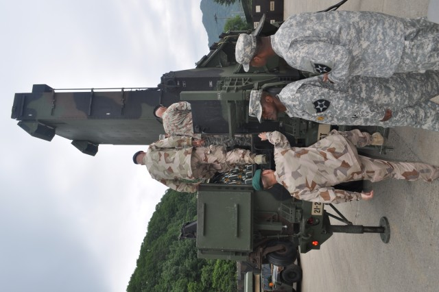 "CAMP CASEY, South Korea "" Swiss and Swedish leaders from the Neutral Nations Supervisory Commission visit 210th Fires Brigade, 2nd Infantry Division on Camp Casey, South Korea June 11, 2013. The 1st Battalion, 38th Field Artillery Regiment, 210th Fires Bde., displays the M270A1 multiple launch rocket system and the AN/TPQ-37 version eight radar in the 333rd Field Artillery Target Acquisition Battery motor pool. This visit is to build a strong relationship between 210th Fires Bde., and the NNSC, and to gain better knowledge of unit capabilities. (U.S. Army photo by Cpl. Kim Han-byeol, 210th Fires Brigade public affairs specialist/Released)."