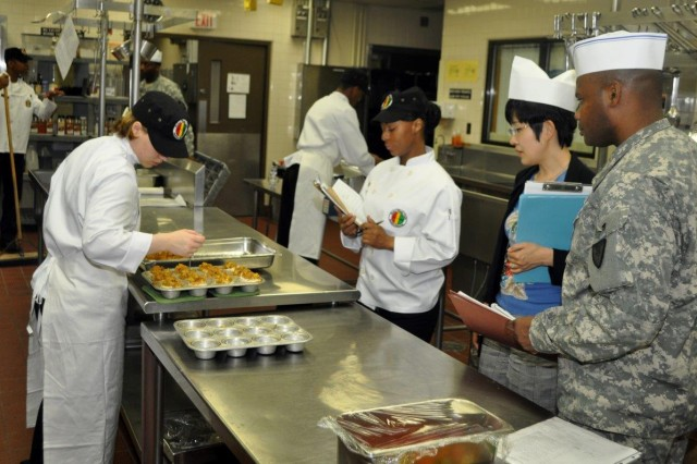 Judges observe a soldier preparing stuffed fish at the Rotor Wash Café Dining Facility on K-16 during the Phillip A. Connelly Competition, June 11. (U.S. Army photo by Cpl. Lim Hong-seo)