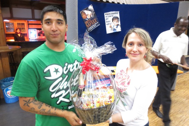 Lt. Col. Michelle L. Bienias, right foreground, commander of U.S. Army Garrison Bamberg, presents Pedro Elizondo, a Soldier at USAG Ansbach, with a gift basket at a music hall at Geiselwind, Germany, as part of a motorcycle rally to promote motorcycle safety June 7. USAG Ansbach, Bamberg and Schweinfurt participated in the Franconia Military Community event.