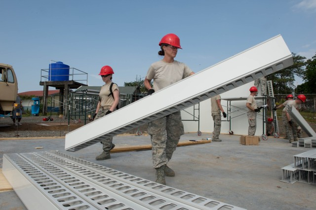 Air Force Senior Airman Amy McDermott, from the 200th Red Horse Squadron in Mansfield, Ohio, right, pre-stages synthetic wall system pieces to erect a wall on a clinic in the town of Escobal, Panama, during the Beyond the Horizon exercise on April 16, 2013. The exercise is a major component of the U.S. military's regional engagement efforts and provides a unique opportunity to train U.S. service members alongside partner-nation personnel, while providing needed services to local communities. (U.S. Army photo by Kaye Richey, U.S. Army South Visual Information)