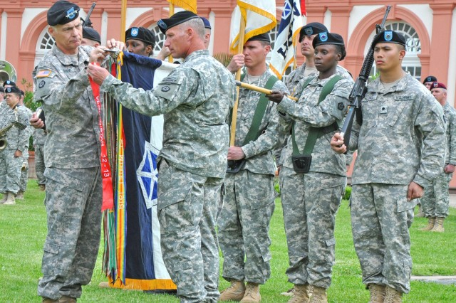 V Corps commander Lt. Gen. James L. Terry (left) and V Corps Command Sgt. Maj. William Johnson place a Meritorious Unit Commendation streamer on the corps colors during the unit's inactivation ceremony at Schloss Biebrich in Wiesbaden, Germany, June 12, 2013.