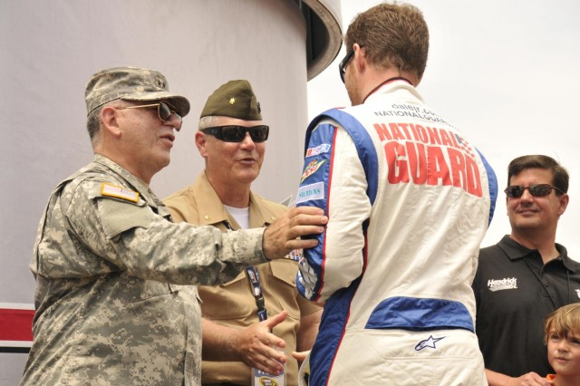 Army Maj. Gen. Francis D. Vavala, the adjutant general of the Delaware National Guard, converses with race car driver Dale Earnhardt, Jr. during opening ceremonies for NASCAR's FedEx 400 at the Dover International Speedway in Dover, Del., June 2, 2013. (U.S. Army photo by Staff Sgt. Brendan Mackie/Released)