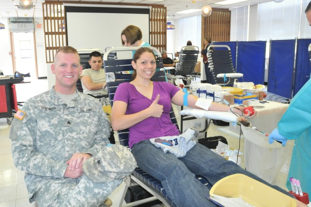 "Erin Brewer, wife of Sgt. Mathew Brewer, left, from the 402nd Field Artillery Brigade, gives the ""thumbs-up"" sign to show that her blood donation is going well during the brigade's blood drive at Fort Bliss, Texas, May 13. More than 50 Soldiers, civilians and Family members volunteered to donate at the drive. (Photo by Staff Sgt. Patricia Deal, 402nd Field Artillery Brigade, Division West, Public Affairs)"