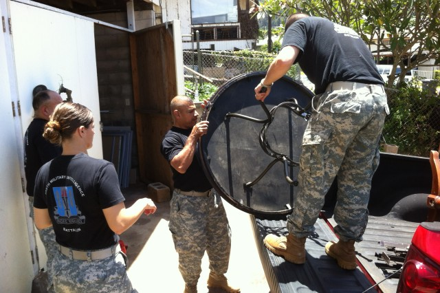 "Soldiers with the 8th Theater Sustainment Command, the Tripler Army Medical Center, and the 25th Infantry Division unload and appliances from a church in Eva Beach to an emergency bed house that will eventually shelter as many as 20 homeless veterans at a time during the ""Soldier for Life"" Veterans Outreach Program, June 11, in downtown Honolulu, Hawaii."