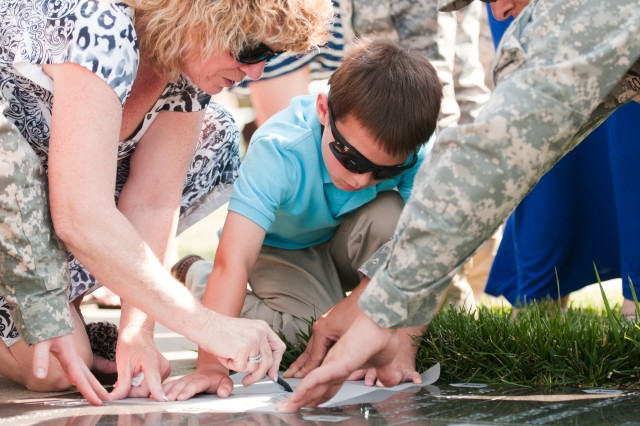 "Loved ones of a fallen 1st Inf. Div. Soldiers trace a brick Wednesday, June 12, at Fort Riley's Victory Park following a rededication ceremony. Ten names were added to the list of 541 who have died while serving with or attached to the ""Big Red One"" in Iraq and Afghanistan."