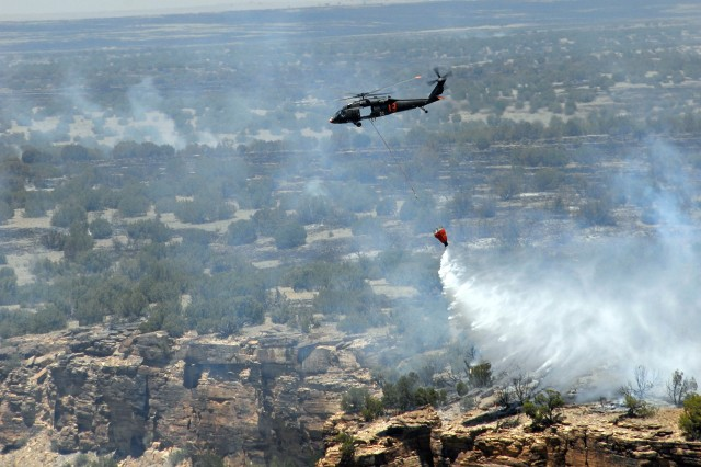 A UH-60 Black Hawk helicopter from the Colorado Army National Guard's 2nd Battalion, 135th General Support Aviation, drops 500 gallons of river water onto a wildfire burning the training range at Fort Carson, Colo., June 13, 2008. Today, aircraft with similar firefighting equipment are fighting the Black Forest fire in El Paso County, Colo.