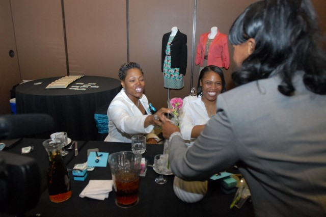 Master Sgt.'s Patrice Glover (left) from Birmingham, Ala., and Tabrina Adams (center) from Deerfield Beach, Fla., receive roses from Sandra Alexandra, Mary Kay consultant and retired Sgt. 1st. Class during the Brunch at Tiffany's symposium April 27 at the Centennial Club at Fort Bliss, Texas. (U.S. Army photo by Sgt. Larry Barnhill, 24th Press Camp Headquarters)