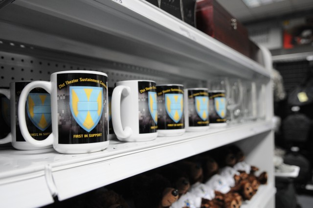 KAISERSLAUTERN, Germany - Coffee mugs bearing the 21st Theater Sustainment Command's logo and motto sit on a shelf at the Military Clothing and Sales Store on Kleber Kaserne, here, June 4.  The 21st TSC now offers memorabilia including play cards, teddy bears, notebooks, lapel pins, sketchbooks, and tote bags for purchase at the Kleber Military Clothing and Sales store. (Photo by Spc. Iesha Howard 21st TSC Public Affairs)