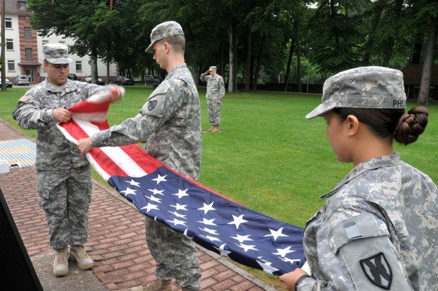 Staff Sgt. Yisey Aponte, a mortuary affairs specialist with the 21st Theater Sustainment Command and a native of Puerto Rico, folds the American flag as Spc. Chase Webb, a native of Cincinnati, and Pfc. Marygrace Phillips, a native of Chicago, both with the 21st TSC, hold the flag during a retreat ceremony on Panzer Kaserne, June 10. Soldiers of the 21st TSC participate in the reveille and retreat ceremonies daily, to include weekends, in recognition of military tradition and in honor of the flag. (Photo by Staff Sgt. Warren W. Wright Jr., 21st TSC Public Affairs)