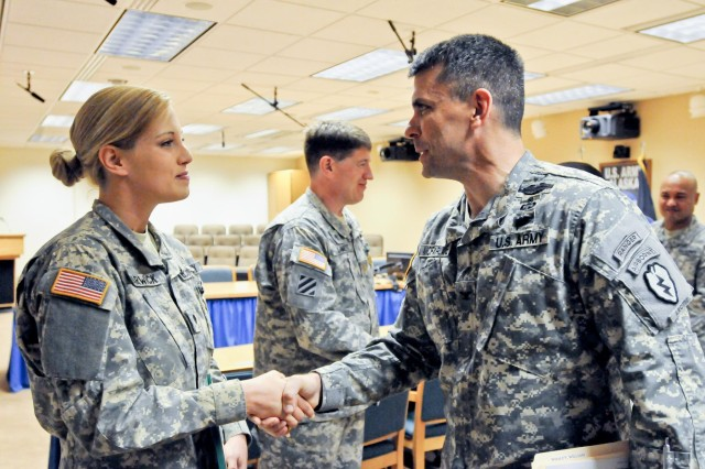 U.S. Army Col. Matthew McFarlane, the commander of the 4th Brigade Combat Team (Airborne), 25th Infantry Division, presents U.S. Army Spc. Kathryn Harwick, a chaplain's assistant, with the 4-25 ABCT Brigade challenge coin for her achievement as being named as part of the United States Army Pacific Command Brigade Unit Ministry Team of the year. Harwick was also presented with an Army Commendation Medal. (Photo by U.S. Army Sgt. Eric-James Estrada/Released)