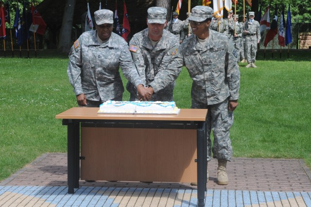 """KAISERSLAUTERN, Germany """" Master Sgt. Patricia Hamilton, left, Col. Michael Snyder, center, and Pfc. Troiasha Hubbard use a saber to cut the Army Birthday Cake during the 21 Theater Sustainment Command's Army Birthday ceremony on Panzer Field, June 13. Hamilton, the 21st TSC financial manager and a native of St. Croix, Virgin Islands, was selected as command's most experienced noncommissioned officer while Hubbard, a military police Soldier assigned to the 230th Military Police Company and a native of Lynchburg, Va. was selected as the command's youngest Soldier.  (Photo by Staff Sgt. Alexander Burnett, 21st TSC Public Affairs)"""