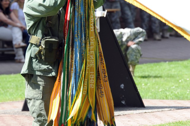 """KAISERSLAUTERN, Germany """" Pfc. Shane T. Wait, a 21st Theater Sustainment Command intelligence analyst and a native of Cleveland, hangs the Army campaign streamers earned during the Vietnam War on the Army colors during the celebration of the Army's 238th birthday on Panzer Field, June 13.   (Photo by Staff Sgt. Alexander Burnett, 21st TSC Public Affairs)"""